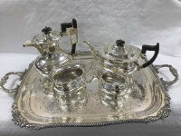 A four piece Sheffield plate tea service on tray with scalloped edge design. (5)