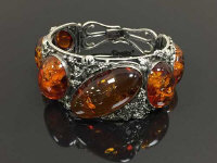 A sterling silver amber cuff bracelet, with vine and leaf decoration amongst six amber panels.