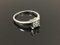 An 18ct white gold diamond ring with four stone square set diamonds, 4g, size N.