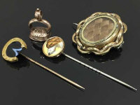 A nineteenth century stick pin with dog head terminal, together with a stick pin with horseshoe terminal, a nineteenth century seal and a Victorian mourning brooch. (4)