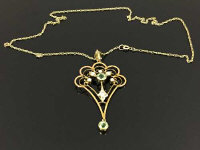 A 9ct gold Edwardian pendant set with seed pearls and peridot upon a 9ct gold chain.