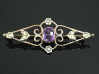 A 9ct gold bar brooch set with seed pearls and amethyst, width 5 cm.