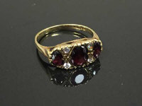A 9ct gold three stone garnet ring, 2.5g, size P.