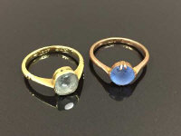 An 18ct gold ring set with a square cut stone, together with a 9ct gold dress ring set with a blue cabochon stone. (2)