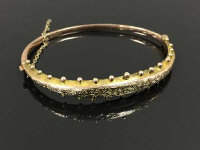 A 9ct gold bangle with studded decorations, 6.8g, 7 cm x 5.5 cm.