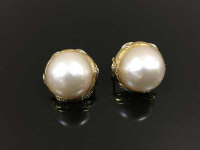 A pair of mabe pearl earrings, mounted in gold and set with diamonds.