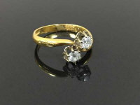 An 18ct gold two stone diamond cross-over ring, size N.