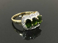 A 9ct gold diamond ring set with three green stones, 2.5g, size M/N.