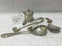 A silver caddy spoon, import marks London 1897, together with a silver straining spoon, silver mustard pot with liner, sugar tongs and mustard spoon. (5)