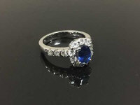 An 18ct white gold diamond and sapphire cluster ring with diamond shoulders, size N.