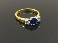 An 18ct gold two stone diamond and sapphire ring, size K.