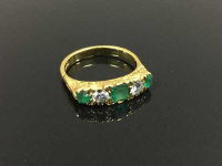 An 18ct gold emerald and diamond ring, size M/N.