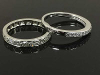 An 18ct white gold diamond half eternity ring, size M, together with a platinum full eternity ring, size J. (2)