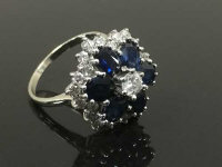 An 18ct white gold sapphire and diamond cluster ring, size L.