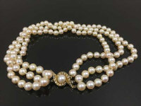 A triple strand of large pearls, on gold clasp set with pearls and diamonds, length 34 cm.