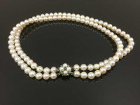 A double strand of pearls with turqoise set gold clasp, length 34 cm.