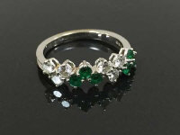 An emerald and diamond half eternity ring in 18ct white gold, size M.