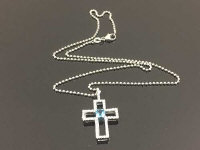 An 18ct white gold diamond and aquamarine cross pendant on chain.