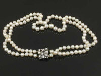 A long double pearl necklace with diamond set white gold clasp, length 42 cm.