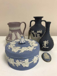 Five items of of Wedgwood Jasper Ware to include lidded powder bowl, diameter 12 cm together with a twin handled urn, mauve colour jug, small spill vase and a brooch. (5)