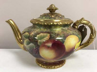 A Royal Worcester gilded teapot decorated with panels of fruit and berries, signed J. Skerrett, the base with black stamp marked RS/BB, height 16 cm