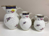 A graduated set of three Coalport gilded china jugs, The Caughley Mask-head (3)