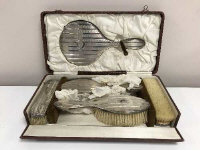 An early twentieth century six piece silver backed dressing table brush set, cased.