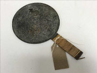 An early twentieth century Japanese hand mirror with embossed decoration, width 14 cm.