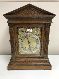An oak cased quarter-striking table clock, the carved case with architectural pediment and pierced sound-frets, the brass and silvered dial signed Gowland, Sunderland, two subsidiary dials for fast/slow and chime/silent, the twin barrel movement striking on two gongs, height 53.5cm