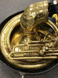 A brass sousaphone, cased.
