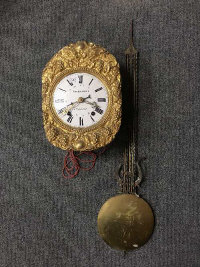 A French wall clock with enamelled dial, with pendulum, the dial signed Theophile Amiet.