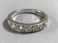 An 18ct white gold diamond half eternity ring, approximately 1ct, size M.