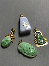 Three mottled jade yellow metal mounted pendants, together with one other similar. (4)