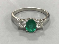 A platinum emerald and two stone diamond ring, size O, approximately 0.5ct.