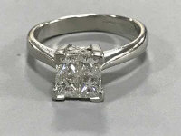 A heavy platinum ring set with four princess cut diamonds, approximately 1.0 carat total weight, 6.8g