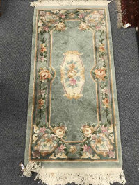 A fringed Chinese rug on green ground, 76 cm x 155 cm.