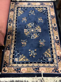A fringed Chinese rug on blue ground, 184 cm x 122 cm.