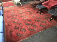 A fringed Afghan carpet on red ground