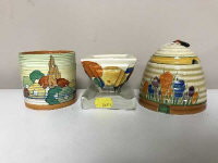 A Clarice Cliff Bizarre Crocus pattern honey pot, with lid, together with a Bizarre Delecia pattern inkwell and a Bizarre preserve pot (no lid).  (3)