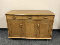 A light elm sideboard fitted with three drawers above cupboards, width 121 cm.