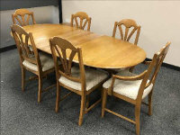 A light elm extending oval dining table, with leaf and six matching chairs, fully extended 203 cm.
