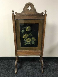 An early 20th century oak fire screen with floral panel, width 60 cm