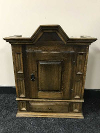An antique style oak wall cabinet fitted with a drawer, width 53 cm