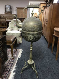 An antique Eastern brass kettle on stand, height 109 cm