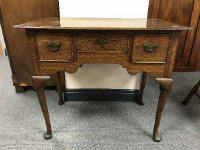 A George III oak low boy fitted with three drawers on pad feet, width 82.5 cm