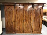 A Victorian Gothic revival four door wardrobe, with arched Gothic detail, inverted break-front cornice, width 268 cm.