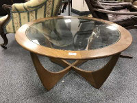 A mid 20th century teak G-Plan glass topped circular coffee table, diameter 83.5 cm.