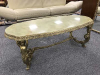 A good quality onyx coffee table mounted on brass trestle type base supported by maidens, width 121 cm.