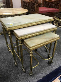 A nest of three gilt brass and onyx tables, width 51 cm.