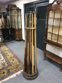 An early 20th century oak revolving snooker cue stand, together with sixteen various cues.